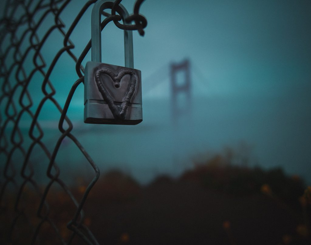 padlock with heart against misty blue background with Golden Gate Bridge tower in distance