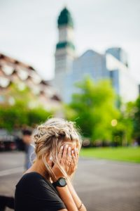 woman weeping into her hands on park bench